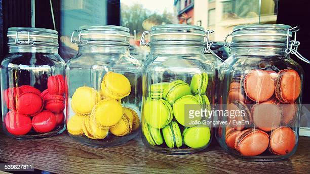 Various Multi Colored Macaroons In Jars On Table