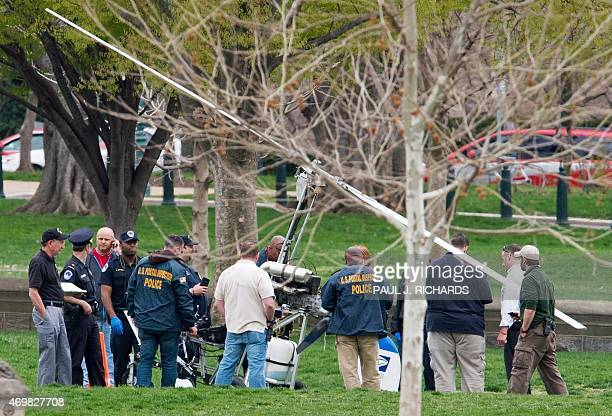 Various officials take a close up look at the scene where a small helo or gyrocopter landed on the US Capitol South Lawn area April 15 in Washington...