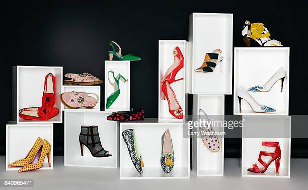 Various pair of shoes in boxes arranged against black background