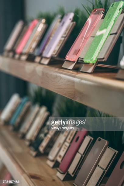 various phone covers displayed on shelves at store - phone cover stock pictures, royalty-free photos & images