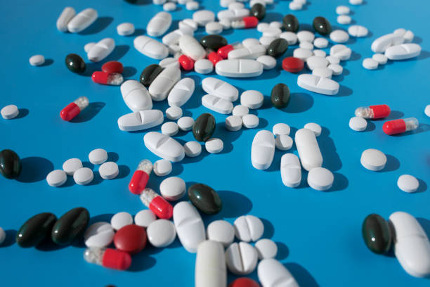Various pills and tablets on the blue background