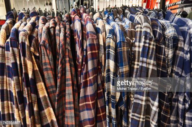 Various Plaid Shirts Hanging On Clothes Rack In Store