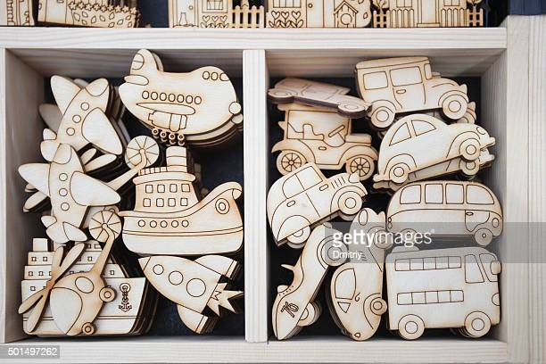 Various plywood toys with pyrograph-made patterns and lines lay ready for painting in wooden box.