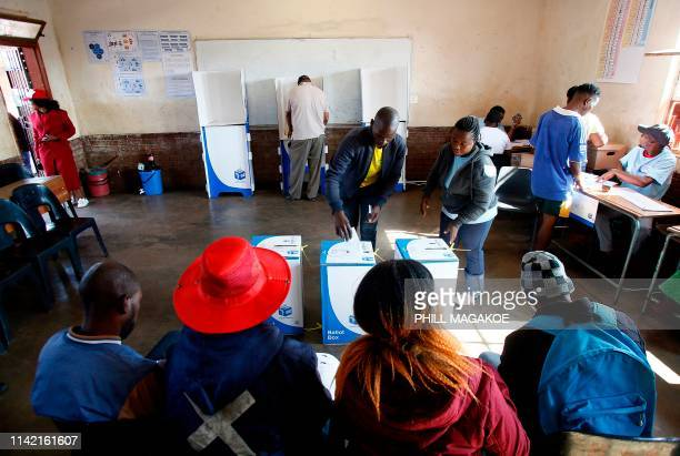 Various political party observors looks on as a man casts his vote at Rakgatla Secondary School polling station during South Africa's national and...