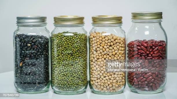 Various Pulses In Mason Jars On Table Against White Background