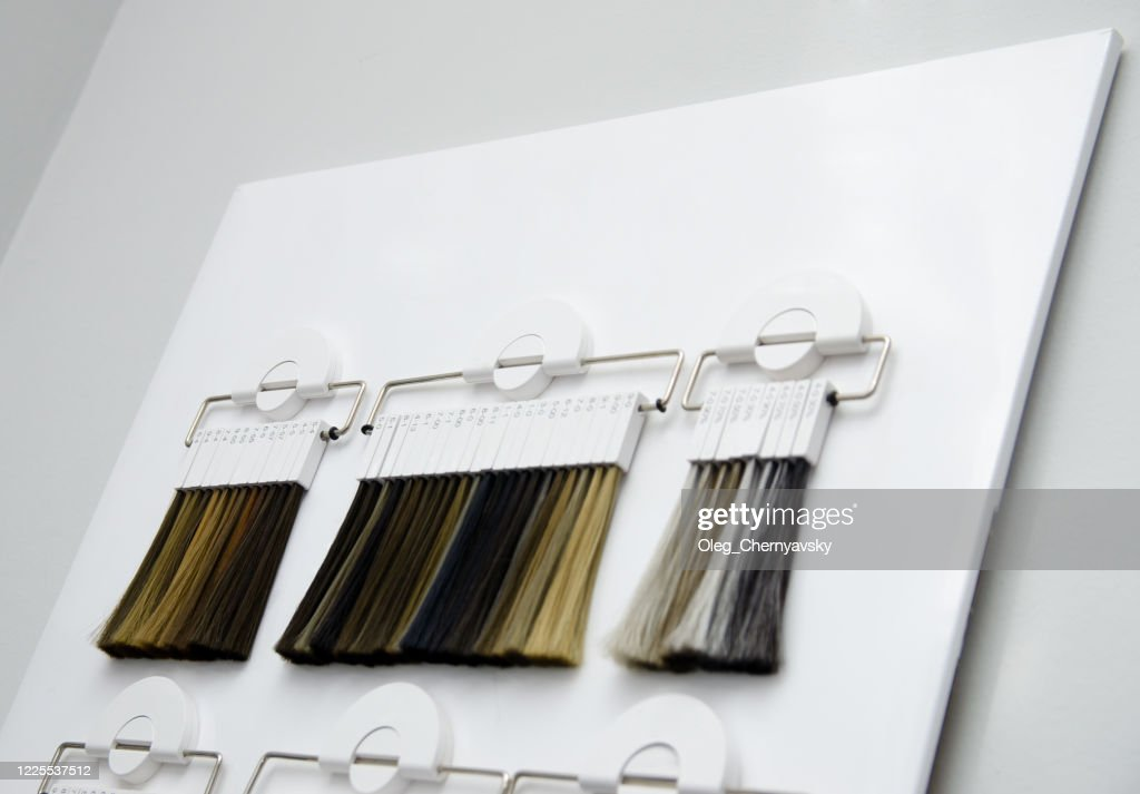 various samples of hair coloring on a special white stand in the salon. hair dye color choice : Stock Photo