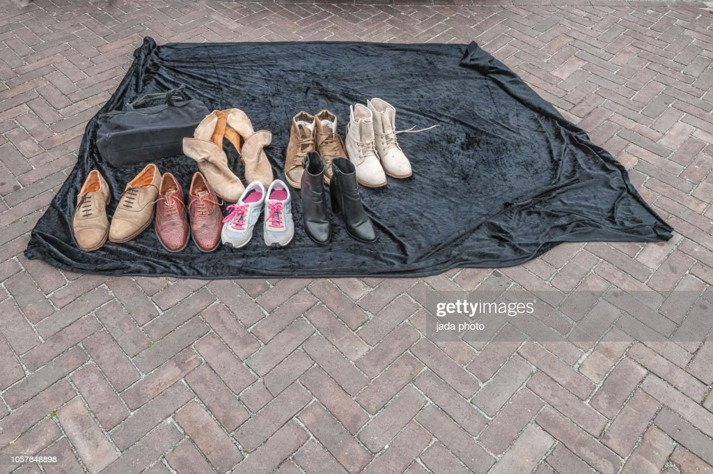 Various Second Hand Shoe On A Black Rug