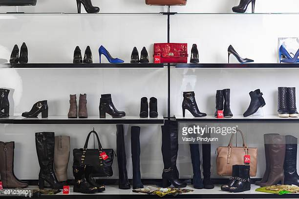 Various shoes and purses displayed on shelves at store