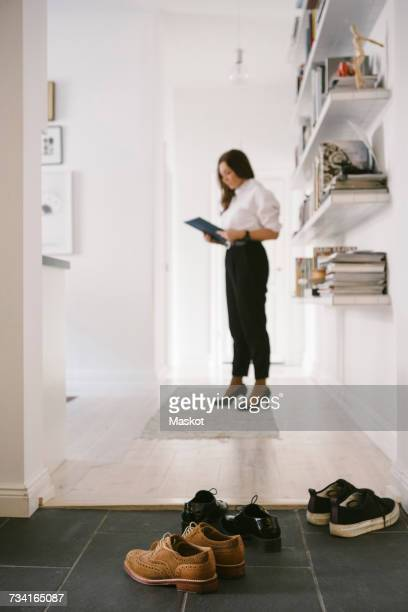 Various shoes on floor with female realtor reading brochure by shelves in background