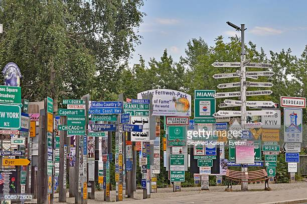 Various Signboards On Street Against Trees