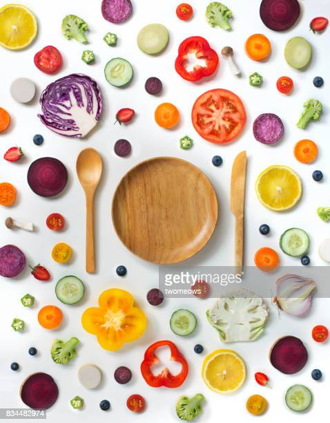 Various sliced fruits and vegetables on white background.