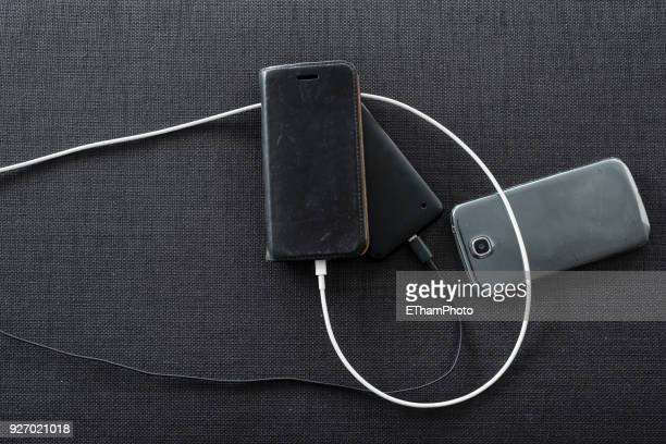 Various smartphones connected to charging cables