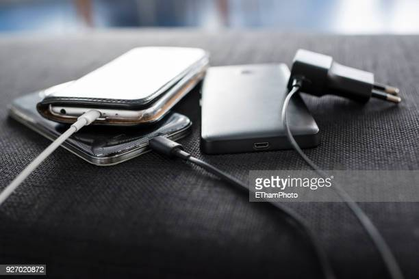 Various smartphones inside appartment connected to mobile phone charging cables