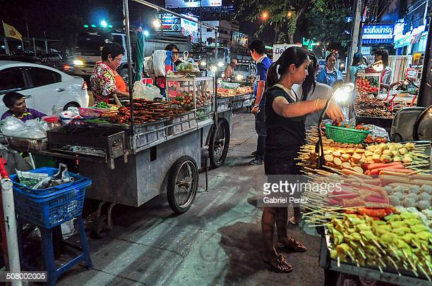 CONTENT] Various Thai foods being sold by vendors at night in downtown Korat Thailand