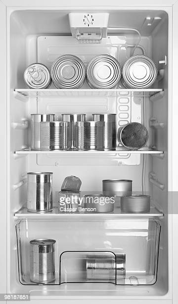 Various tin cans of food in a refrigerator