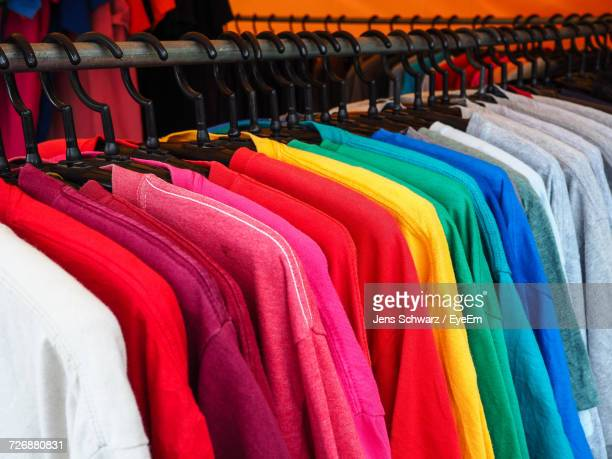 various t-shirts for sale on clothes rack at shop - clothes rack stock pictures, royalty-free photos & images