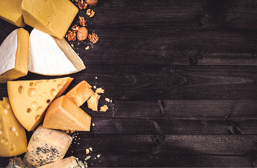 Various types of cheese on black wooden background with copy space 1183547782