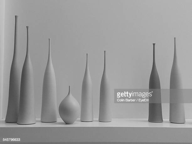 various urns on counter against white wall - urn stock pictures, royalty-free photos & images