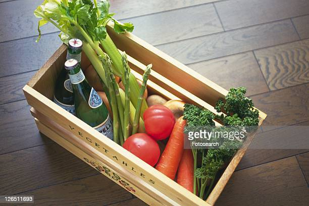 Various vegetables and two wine bottles in wooden box, Differential Focus