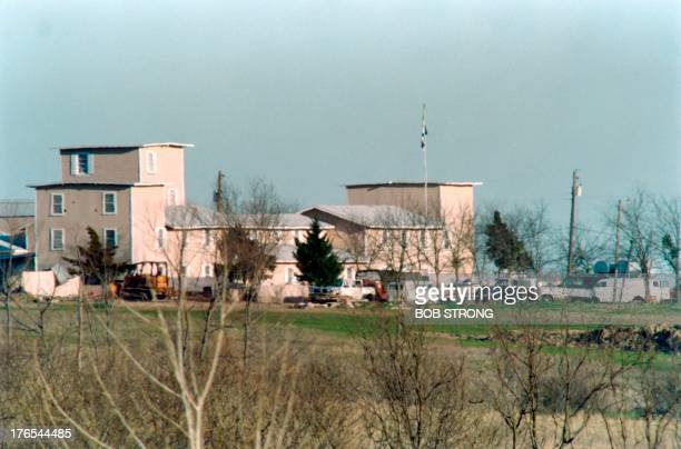 Various vehicles sit in front of the Branch Davidian religious compound in Waco on March 07 1993 as the armed stand off between the religious cult...