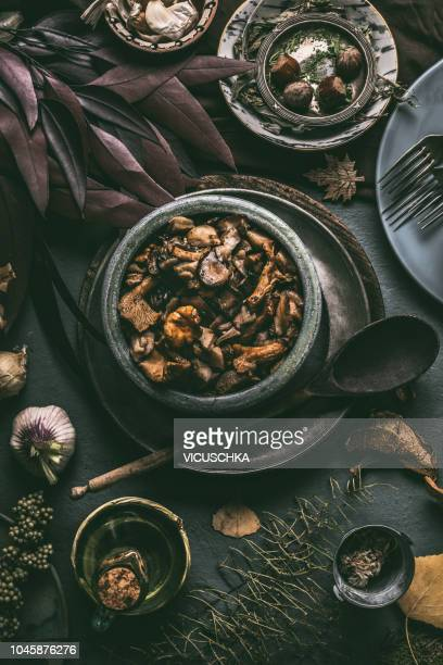various wild forest mushrooms in bowl with aged wooden cooking spoon, dark vintage , top view - uncultivated stock pictures, royalty-free photos & images