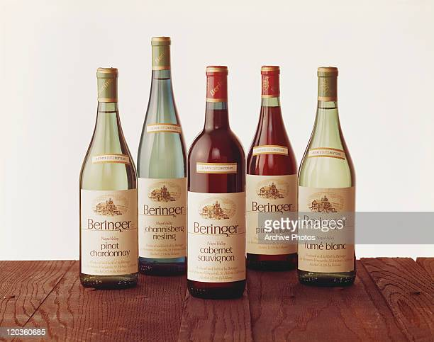 Various wine bottles on table against white background, close-up