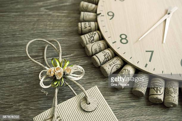 Various wine cork around a wall clock and a decorated bag.