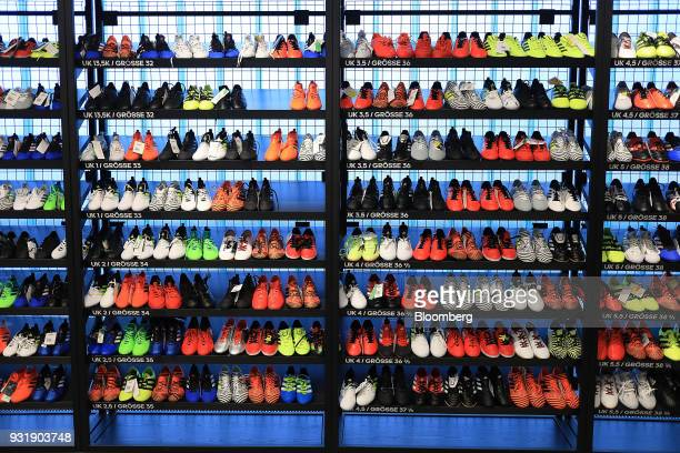 9829736f7b Variously colored soccer boots sit on shelves inside the Adidas AG outlet  at the company s headquarters