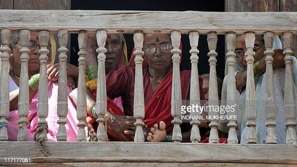 VarkariHindu pilgrims rest on the woden balcony of a guesthouse as they await the start of the annual pilgrimage at the temple of Saint Dnyaneshwar...