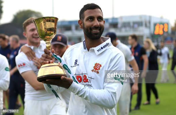Varun Chopra of Essex lifts the County Championship trophy during day three of the Specsavers County Championship Division One match between Essex...
