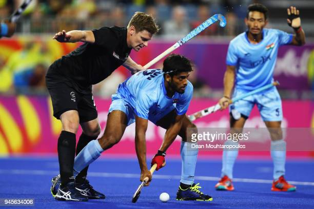 Varun Kumar of India battles for the ball with Stephen Jenness of New Zealand during the Men's Semifinal match between India and New Zealand on day...