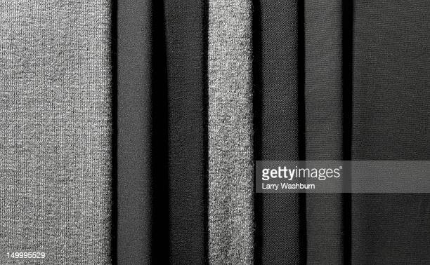 Varying shades of gray textiles hanging in a row