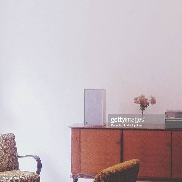 Vase and speaker on end table with cropped chairs in foreground