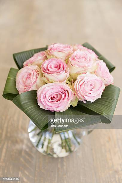 Vase of flowers Laceedged pastel pink roses in an elegant bouquet style floral arrangement with banana leaves in glass jug