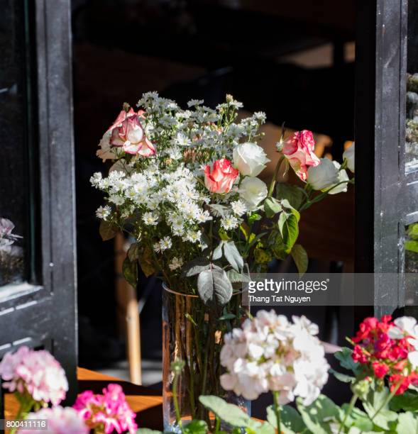 Vase of flowers on desk by window