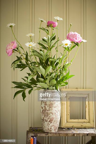 A vase of peonies and daisies and an empty picture frame