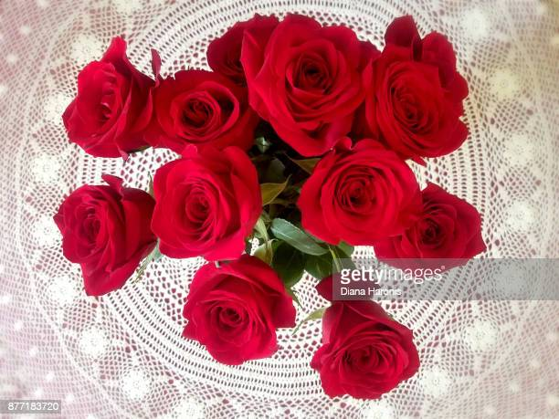 a vase of red roses on a lace tablecloth taken from above. - doily stock photos and pictures