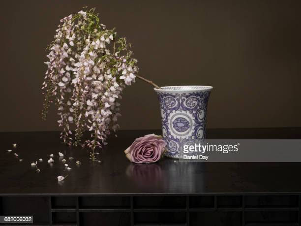Vase on a metal table with flowers spilling out