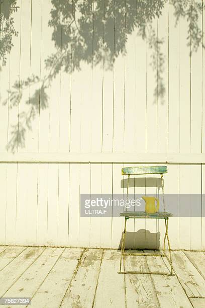 Vase on chair on wooden porch