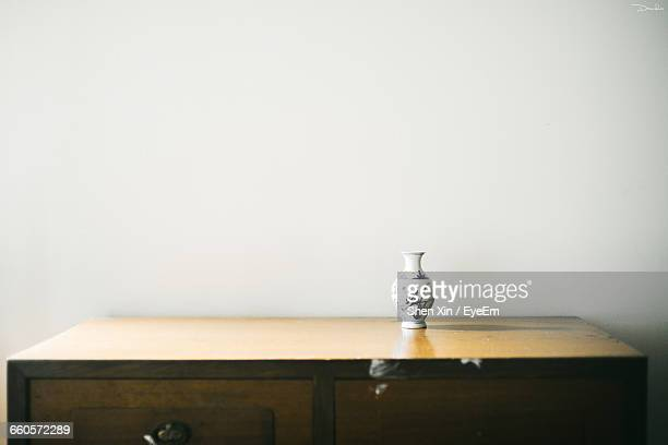 Vase On Wooden Table Against Wall At Home