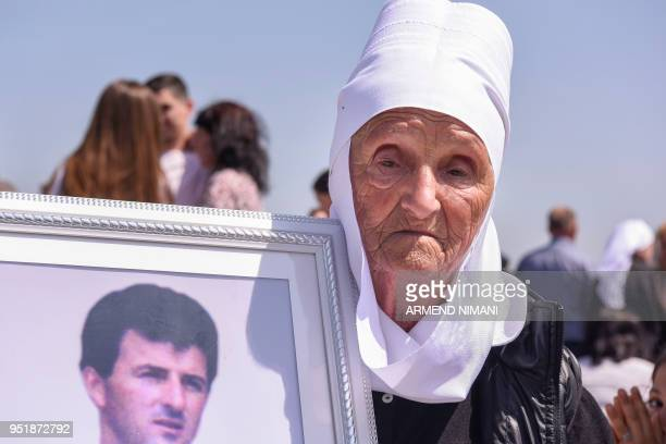 Vase Tahiraj holds a portrait of her son Halil Tahiraj killed during the Kosovo war as she attends a ceremony marking the Day of Missing Persons on...