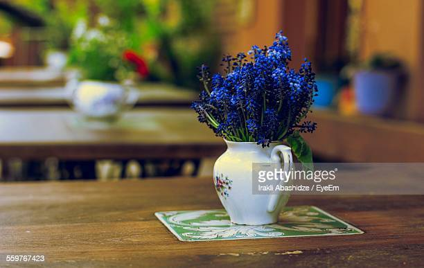 Vase With Blue Flowers On Table