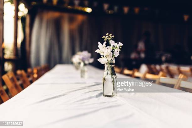 vase with small bunch of flowers on white table - wedding stock pictures, royalty-free photos & images