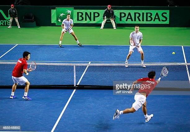 Vasek Pospisil and Daniel Nestor of Canada and Go Soeda of Japan look on as Yasutaka Uchiyamareturns a shot during their Davis Cup doubles match...