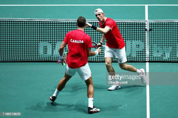 Vasek Pospisil and Denis Shapovalov of Canada celebrate winning the first set in the quarter final doubles match between Australia and Canada during...