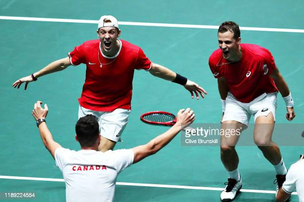 Vasek Pospisil and Denis Shapovalov of Canada celebrate with Canada team captain Frank Dancevic after winning the match in the quarter final doubles...