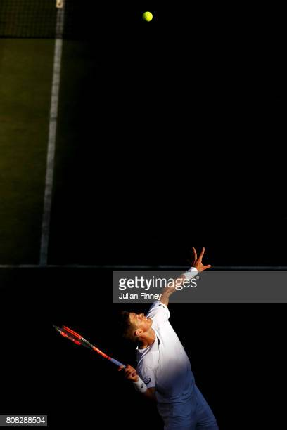 Vasek Pospisil of Canada serves during the Gentlemen's Singles first round match against Dominic Thiem of Austria on day two of the Wimbledon Lawn...