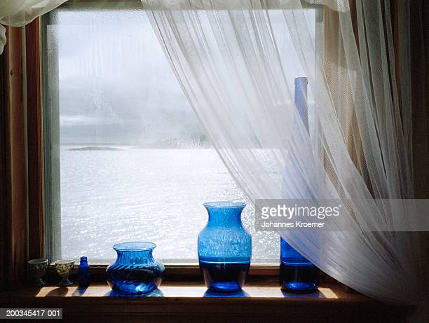 Vases on windowsil overlooking lake