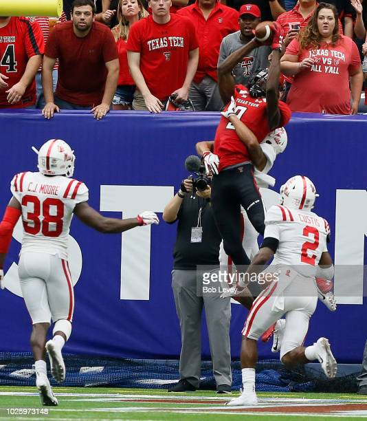 J Vasher of the Texas Tech Red Raiders goes up between CJ Moore of the Mississippi Rebels and Montrell Custis for a reception but dropped the ball...