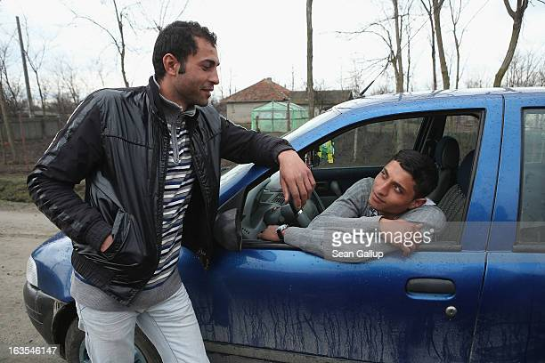 Vasile Nedelcu and his buddy Florin Arapu both of them ethnic Roma hang out at Vasile's car on March 11 2013 in Dilga Romania Vasile's mother works...